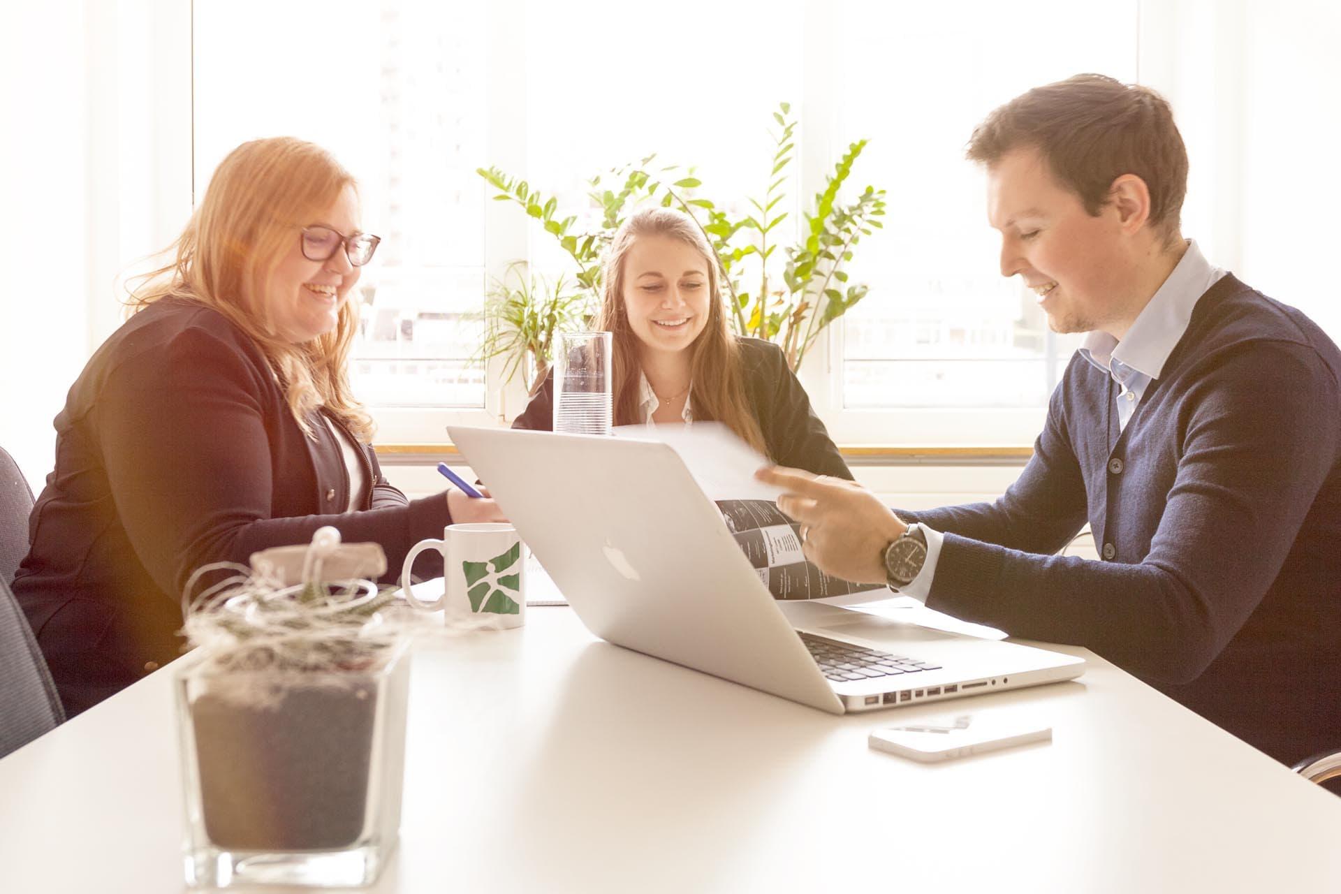 Zwei Frauen und ein Mann im Meeting